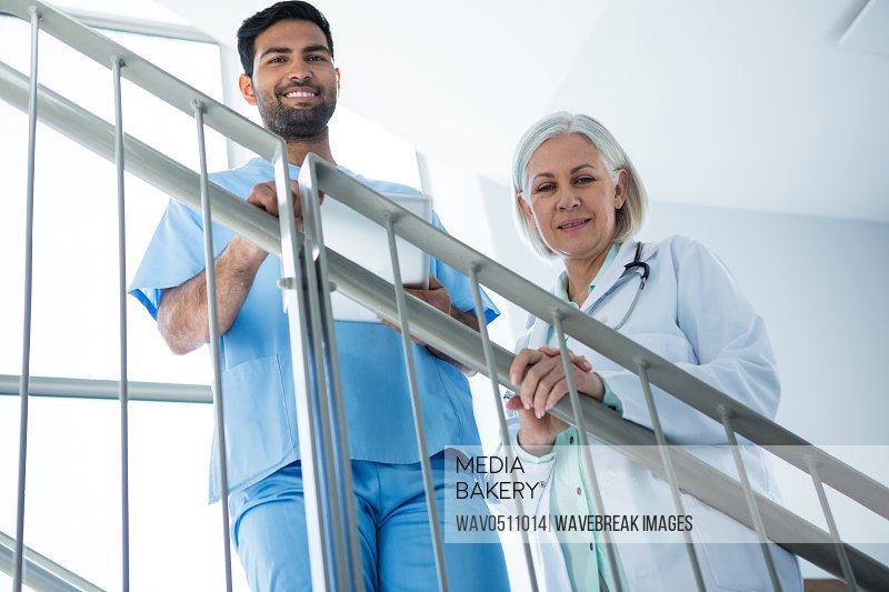Portrait of doctors smiling while standing on staircase in hospital