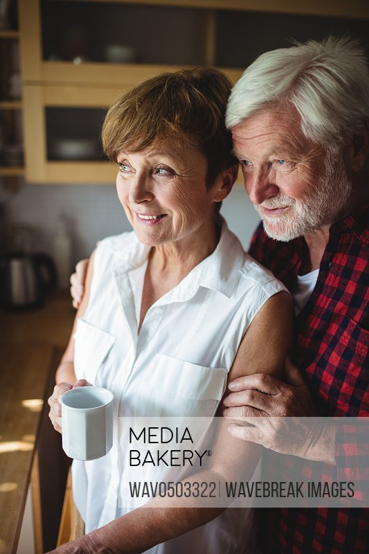 Senior couple standing in kitchen at home
