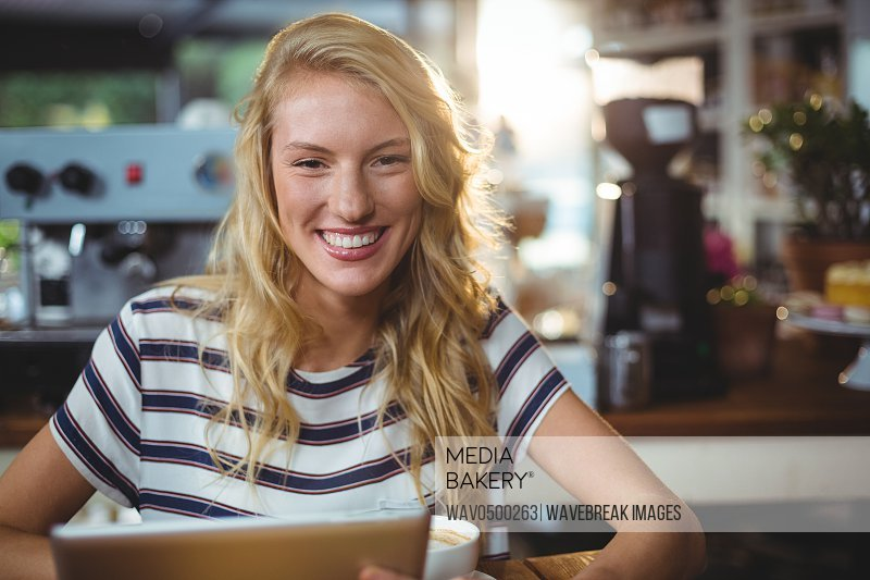 Portrait of woman sitting in a cafe using digital tablet