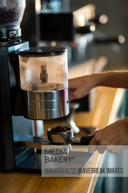 Waiter holding portafilter filled with ground coffee in cafA?