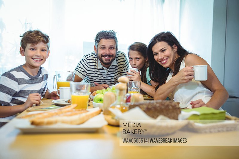 Portrait of happy family having breakfast together at home