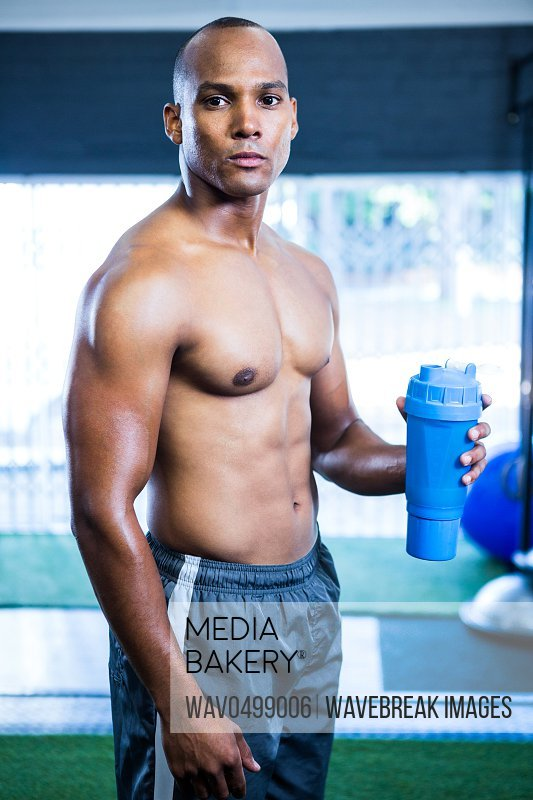 Portrait of muscular shirtless athlete holding bottle in gym