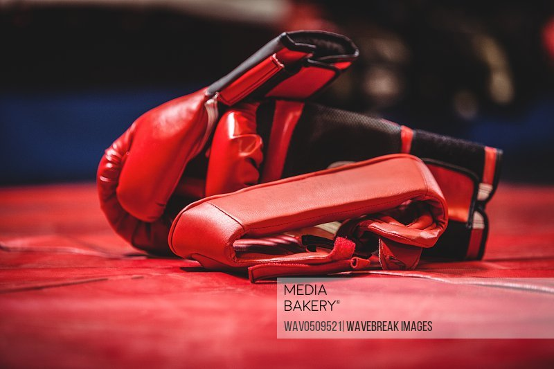 Pair of red boxing gloves on red surface