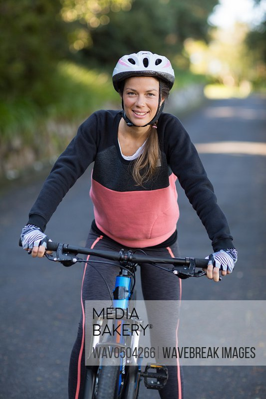 Female biker with mountain bike on the countryside road