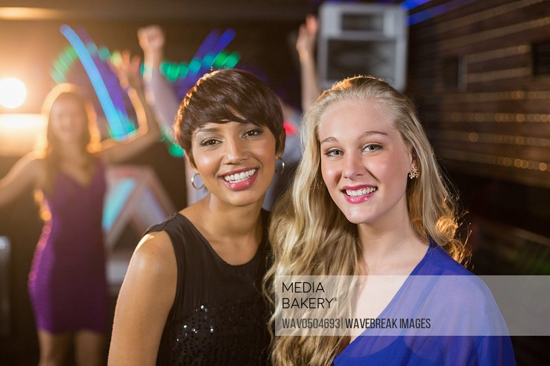 Portrait of smiling two beautiful women standing together in bar