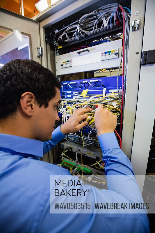 Close-Up of technician checking cables in a rack mounted server