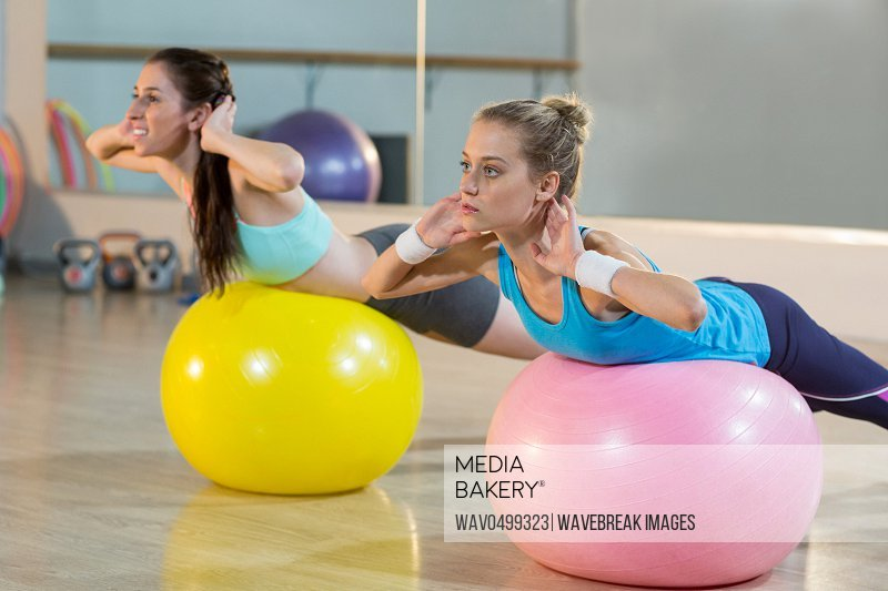 Two women exercising on exercise ball in gym