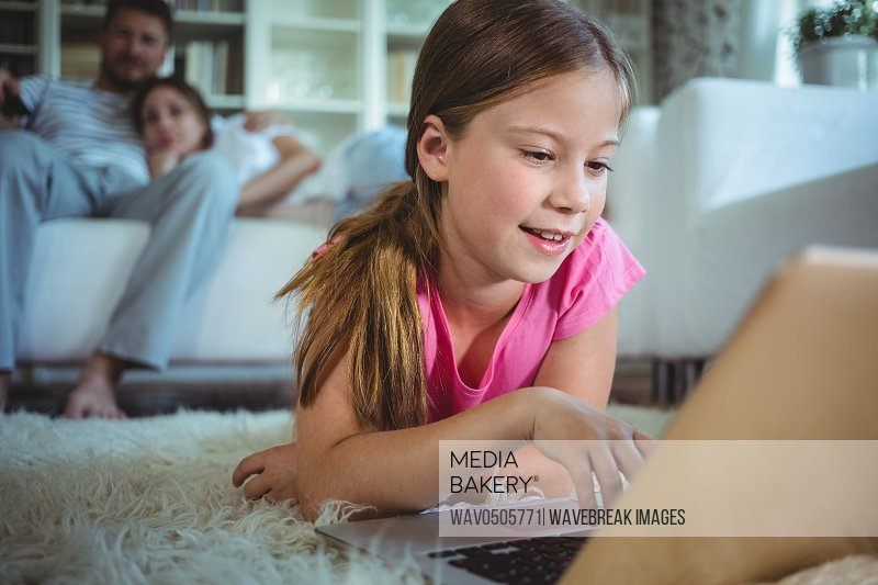 Girl lying on the floor and using laptop while parents sitting on sofa
