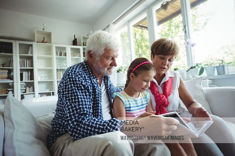 Grandparents and granddaughter looking at photo album in living room at home