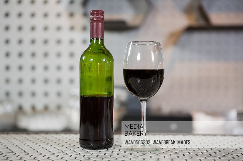 Glass of red wine and bottle on counter in bar