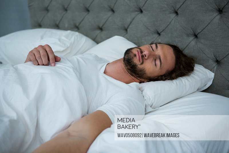Man sleeping on his bed in bedroom at home
