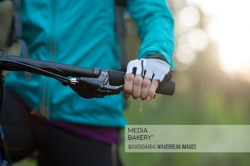 Mid-section of female biker with mountain bike in countryside