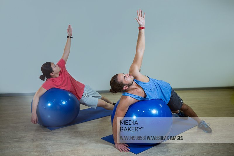 Men exercising with exercise ball in gym