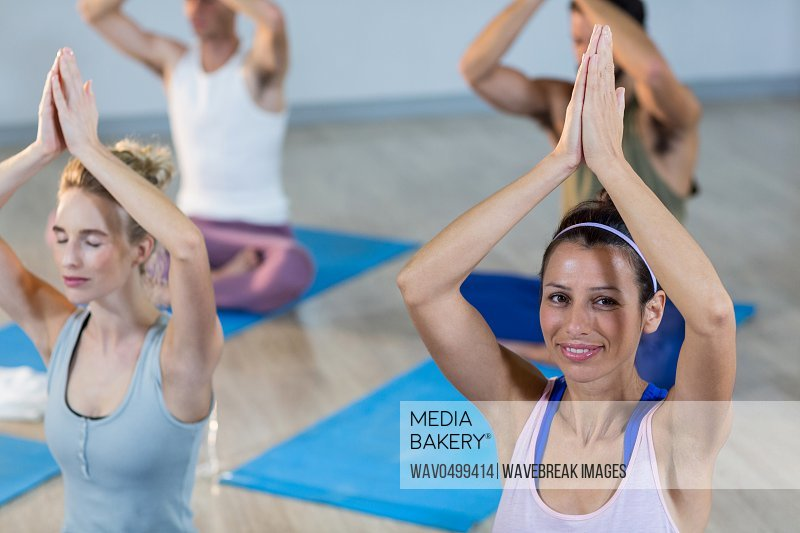 Two beautiful women performing yoga in gym