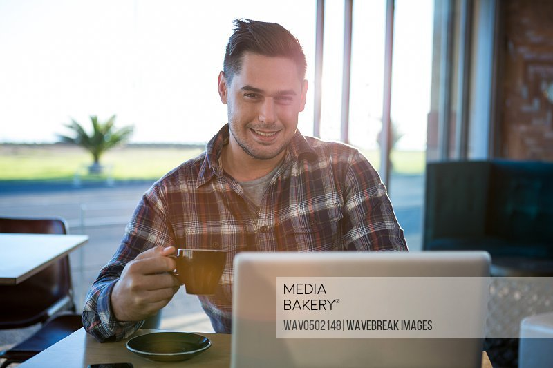Portrait of smiling man using laptop while having coffee in cafeteria
