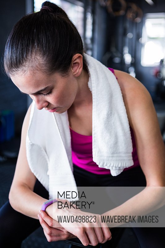 Female athlete checking time while sitting in gym