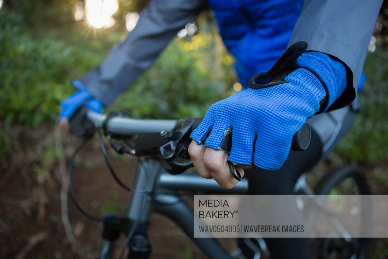 Mid section of male mountain biker riding bicycle in the forest
