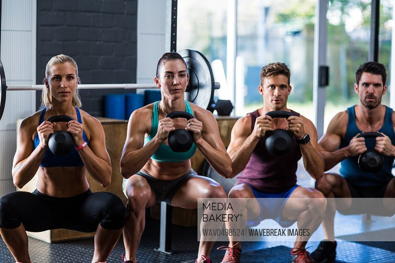 Portrait of friends holding kettlebells while crouching in gym