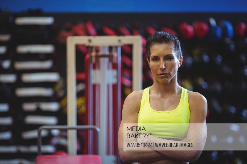 Sportswoman standing with arms crossed in fitness studio