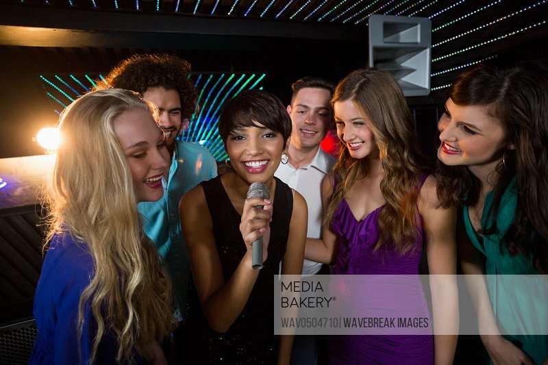 Group of happy friends singing song together in bar