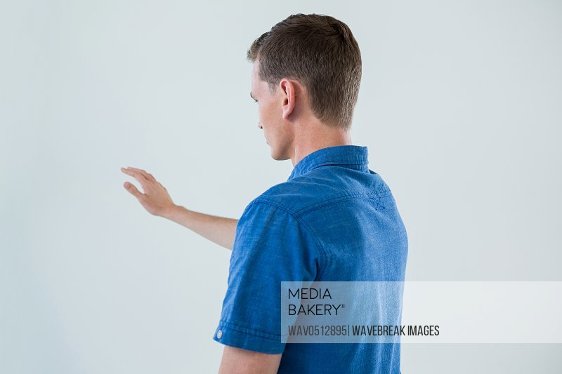 Man touching an invisible screen against white background