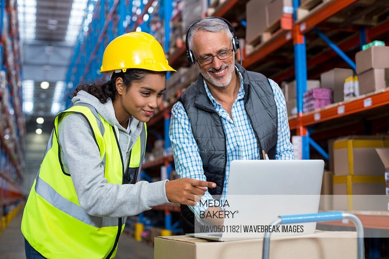 Warehouse manager and female worker using laptop in warehouse