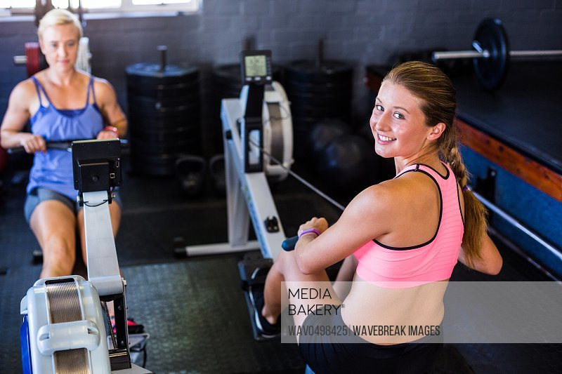 Portrait of smiling woman using row machine in gym
