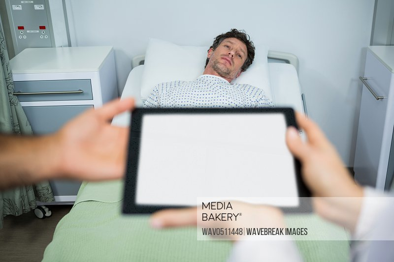 Doctors using digital tablet in ward while consulting patient