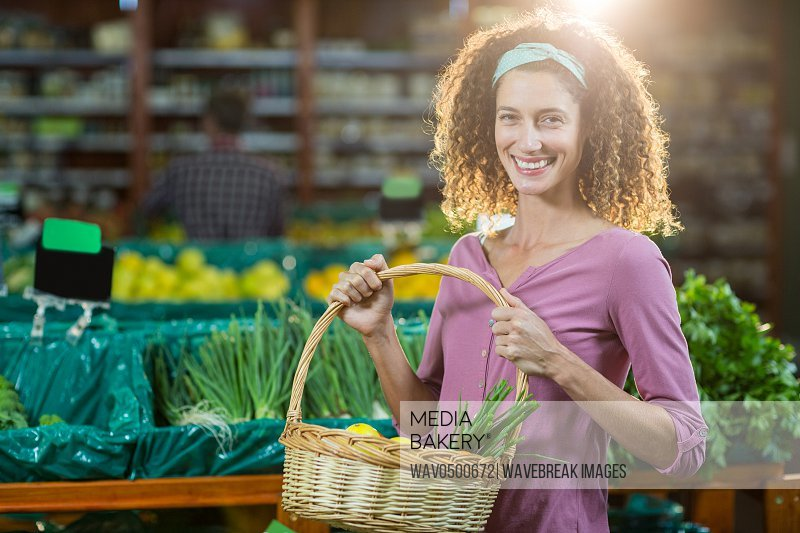 Portrait of smiling woman holding basket of vegetables in organic section of supermarket