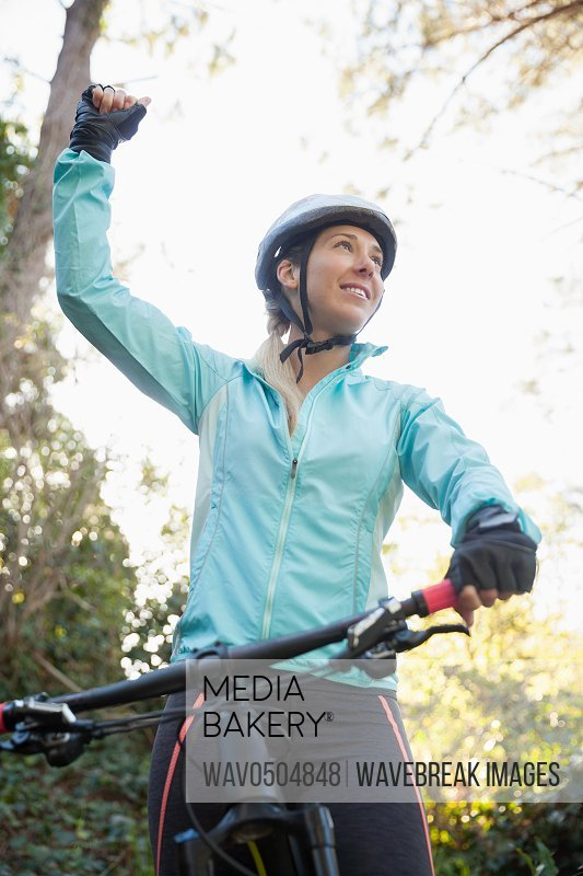 Excited female mountain biker in the forest on a sunny day