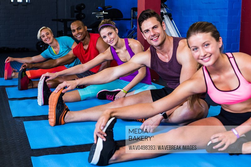 Portrait of smiling people doing stretching exercise while sitting in gym