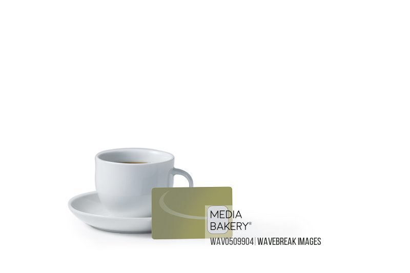 Close-up of black tea with credit card on white background