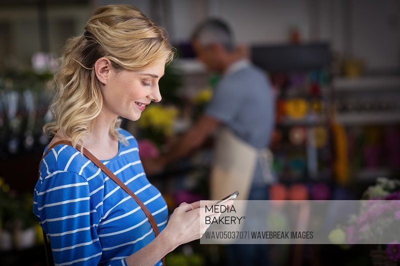 Smiling woman using mobile phone in flower shop