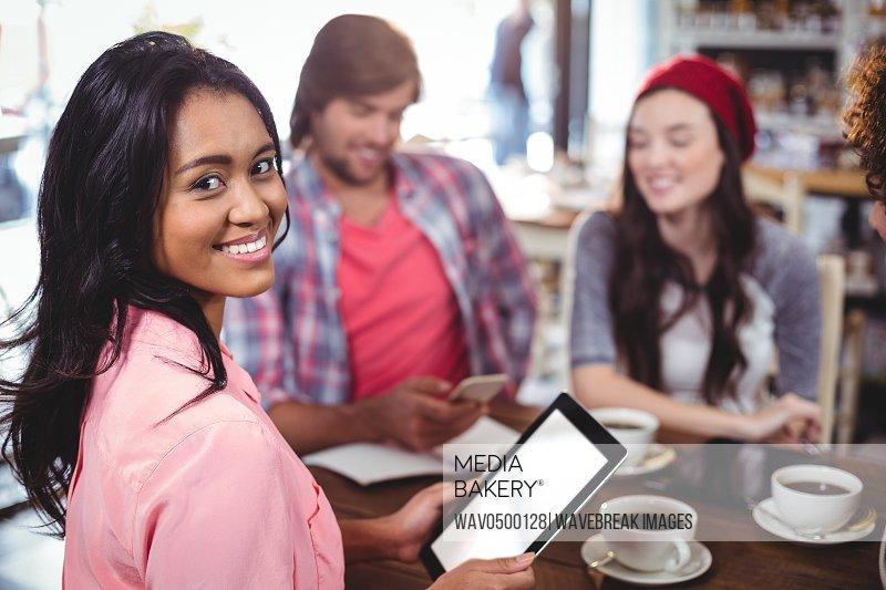 Portrait of smiling woman using digital tablet in cafe