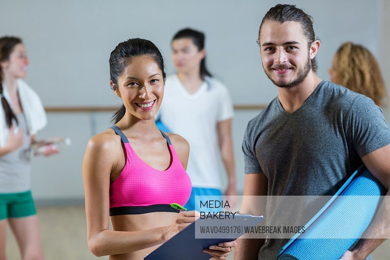 Portrait of female trainer helping man on her work out routines in fitness studio
