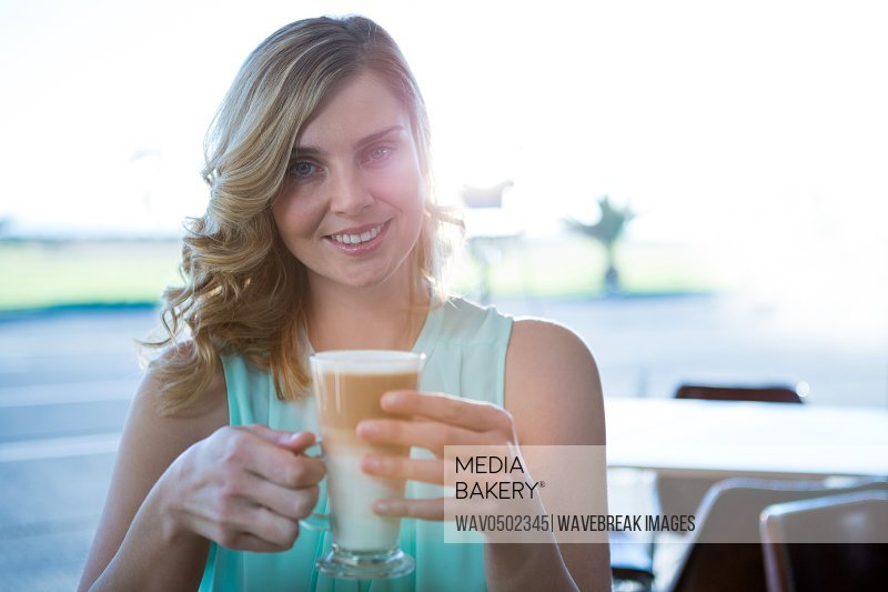 Portrait of smiling woman holding a coffee cup in the coffee shop