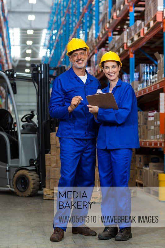 Portrait of smiling warehouse workers standing together in warehouse