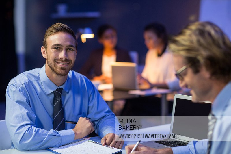 Smiling businessman preparing document in conference room at office