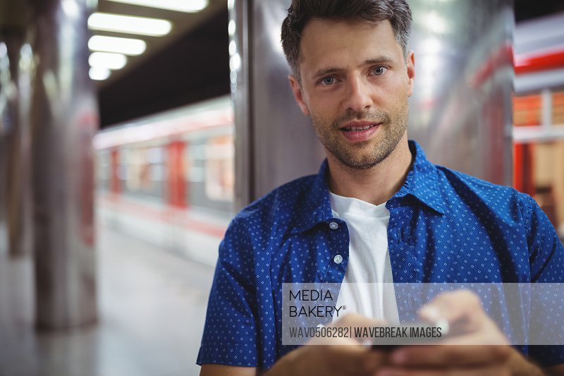 Portrait of handsome man using mobile phone on railway station