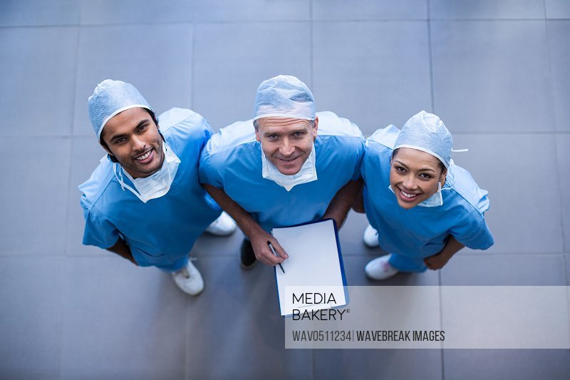 Portrait of surgeons with medical reports in hospital corridor