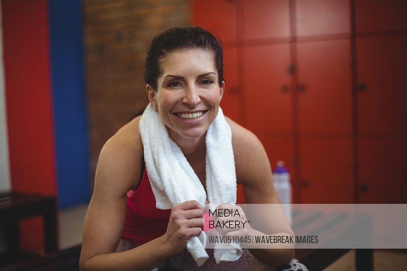 Portrait of cheerful woman sitting in locker room after workout