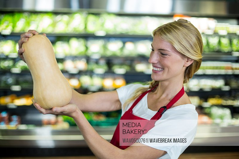 Smiling female staff holding a vegetable in organic section of supermarketA�