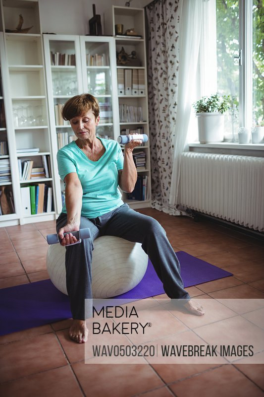 Senior woman exercising with dumbbells on exercise ball at home