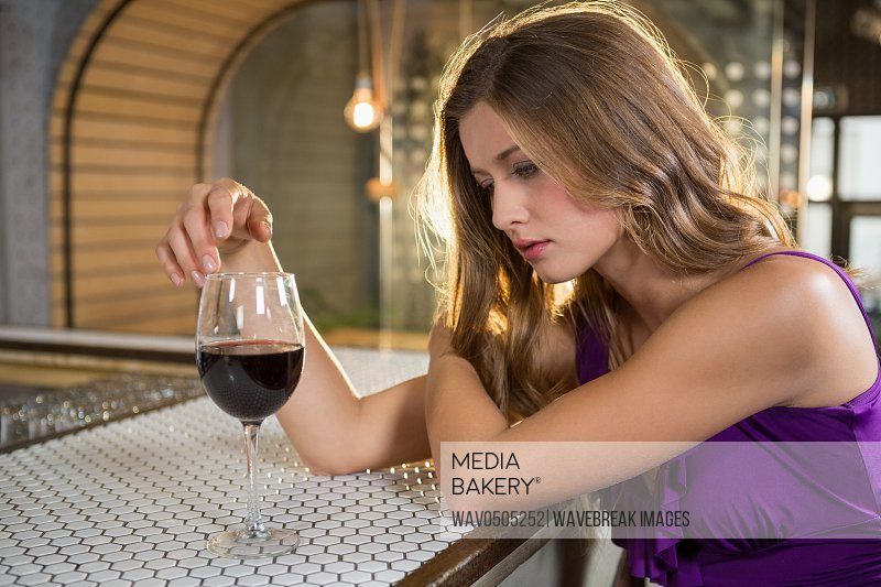 Thoughtful woman having red wine at bar counter in bar