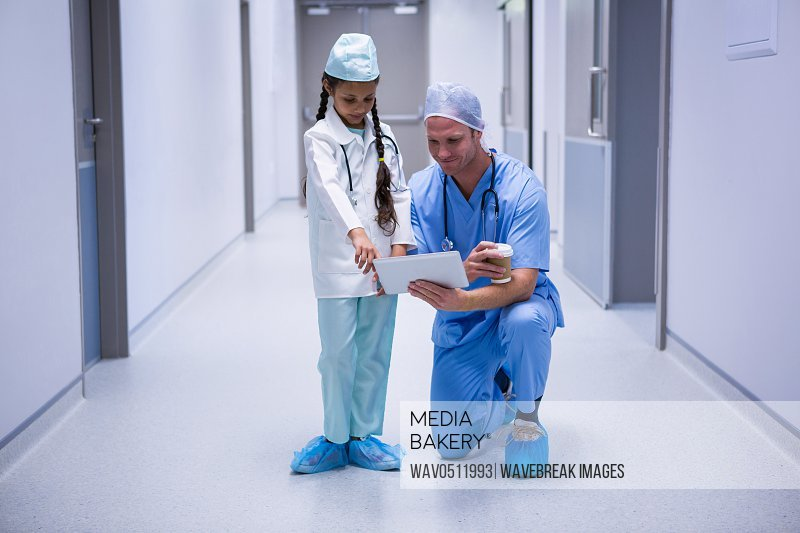 Smiling doctor and girl using digital tablet in corridor at hospital