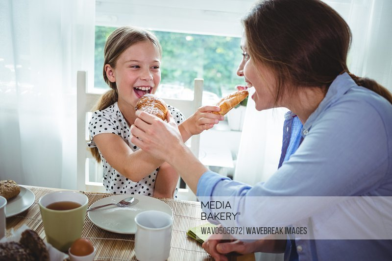 Mother and daughter feeding croissant to each other while having breakfast at home