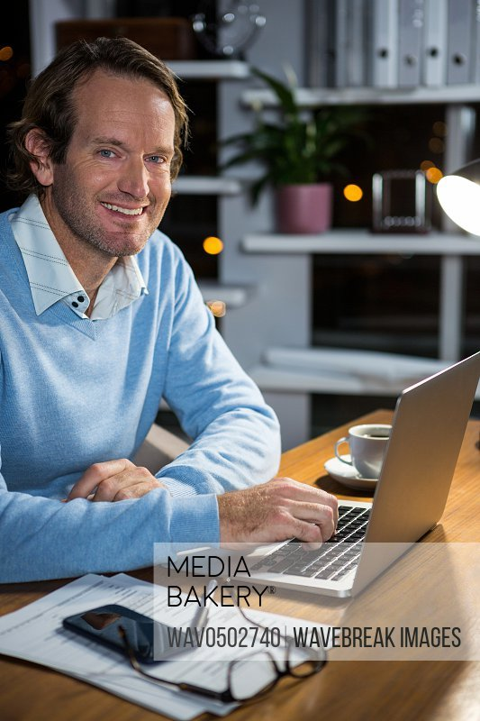 Portrait of businessman working on laptop in office at night