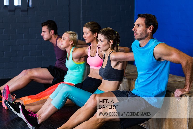 Male and female athletes exercising on wooden box in gym