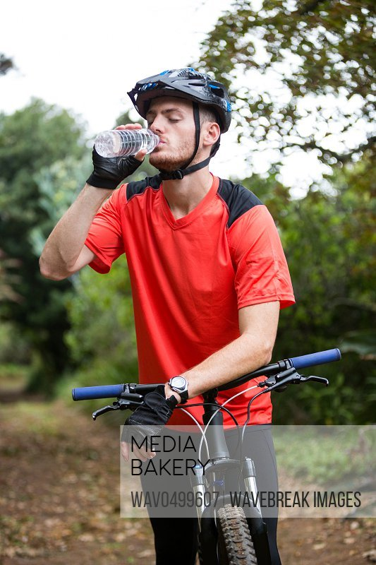 Male cyclist drinking water in countryside