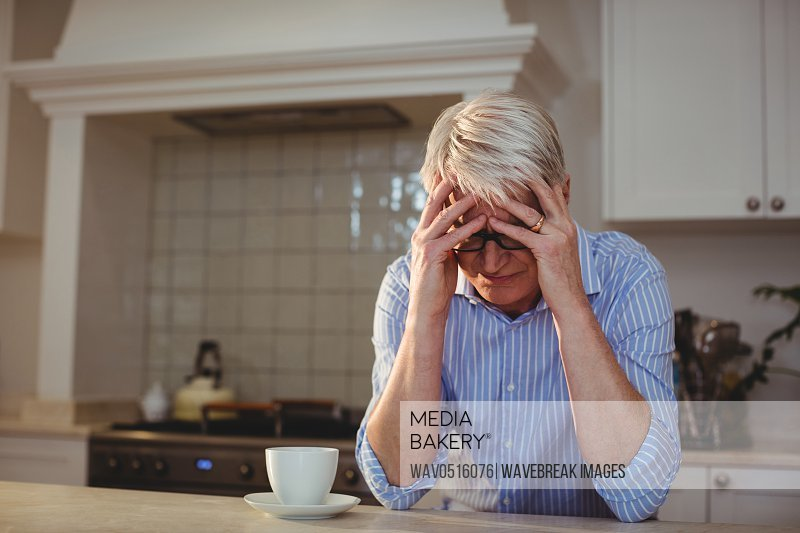 Worried senior man sitting with a cup of coffee